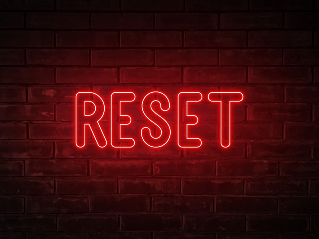 Reset - neon light word on brick wall background // business