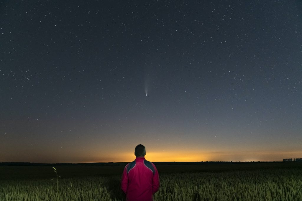 Silhouette of a man standing at night in a field outside the city